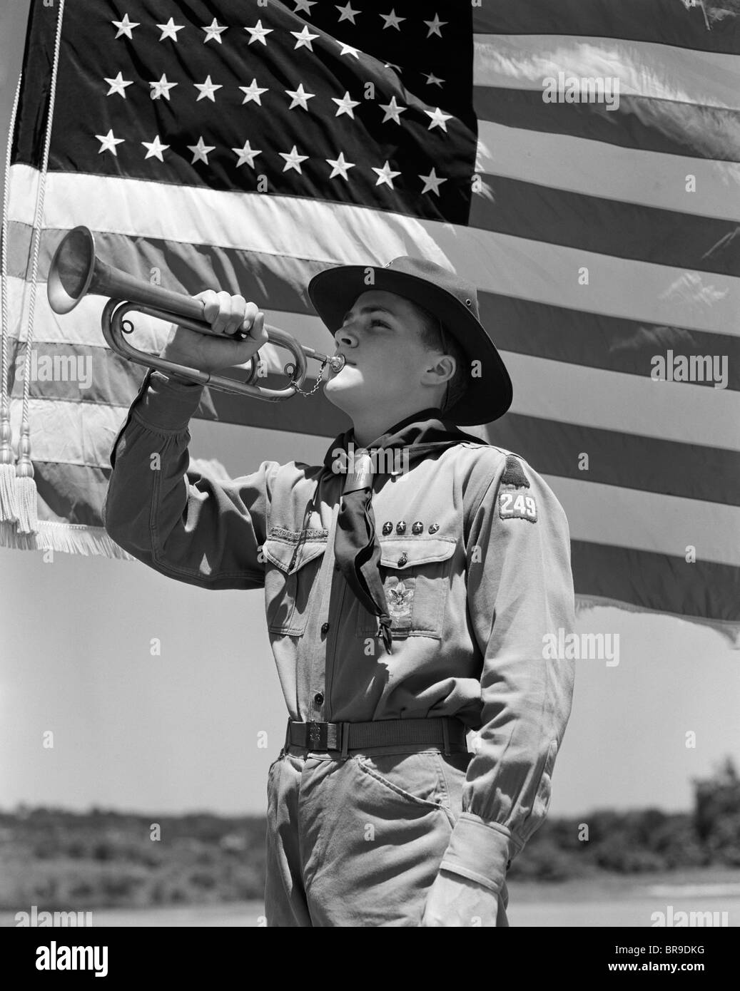 S Boy Scout Playing Bugle In Front Of 48 Star American