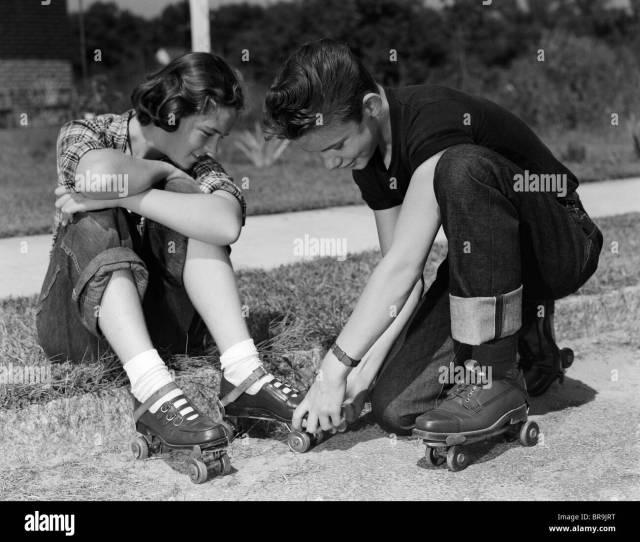 S Teen Boy Helping Girl Put On Metal Roller Skates Sitting On Sidewalk Stock Image