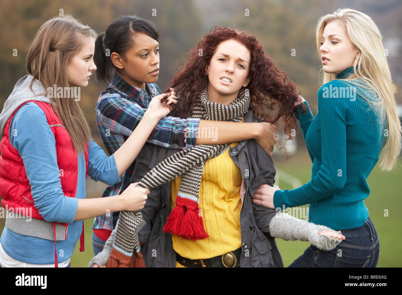 Group Of Female Teenagers Bullying Girl Stock Photo