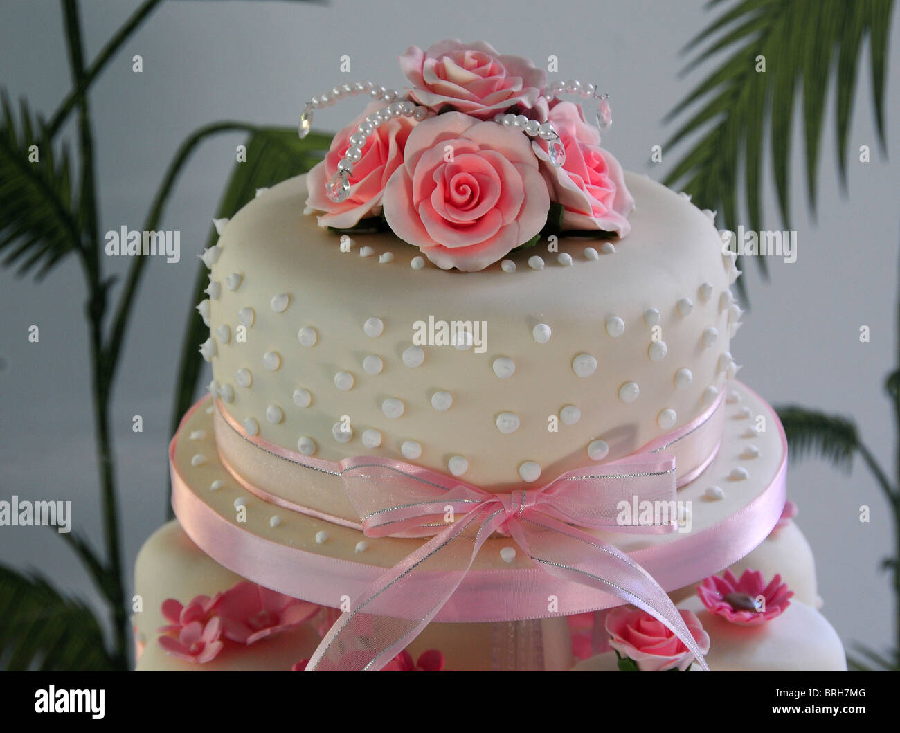 The top tier of a pink and white wedding cake made up with cup cakes     The top tier of a pink and white wedding cake made up with cup cakes and  decorated with a pink ribbon and roses  Dorset  UK 2009