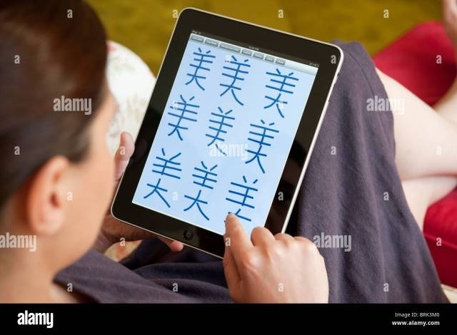 Woman practicing to write mandarin Chinese characters on an iPad