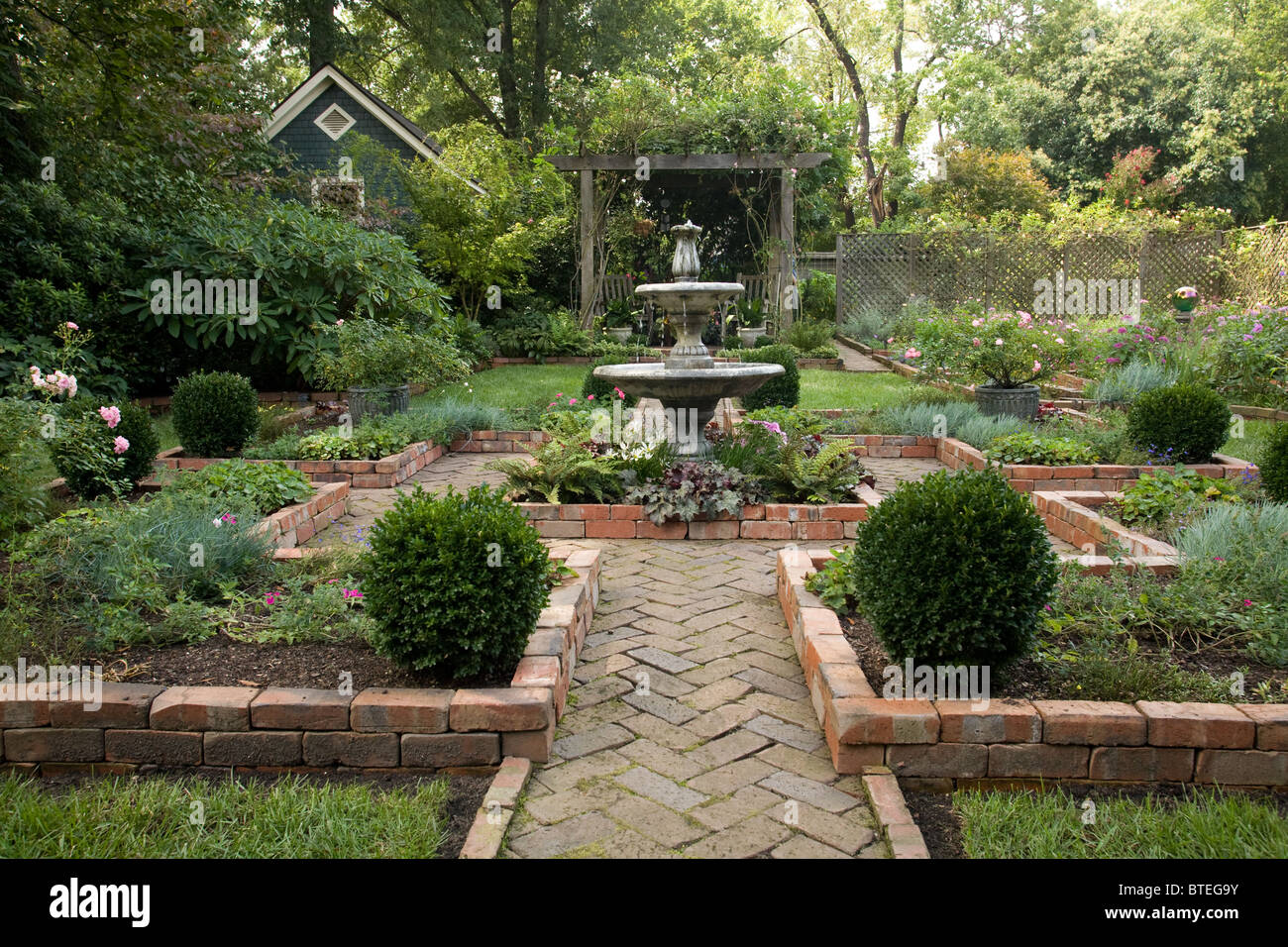 Brick Courtyard With Water Fountain And Gardens Stock