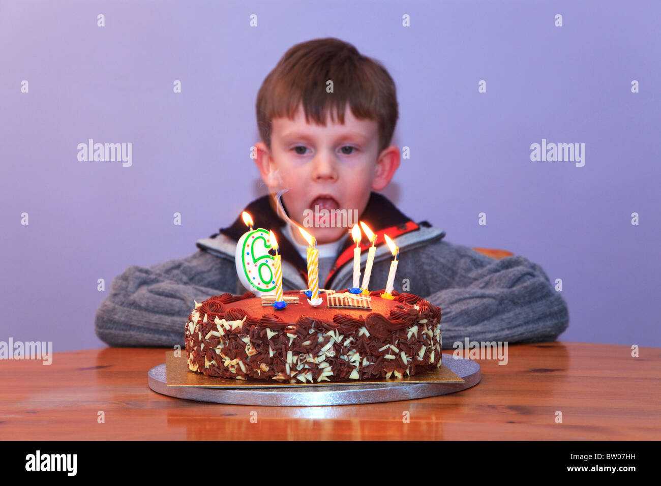 A 6 Year Old Boy Looking At The Candles On His Birthday Cake Stock Photo Alamy