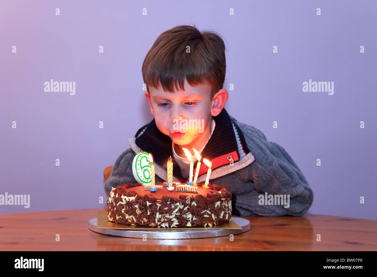 A 6 Year Old Boy Blowing Out The Candles On His Birthday Cake Stock Photo Alamy