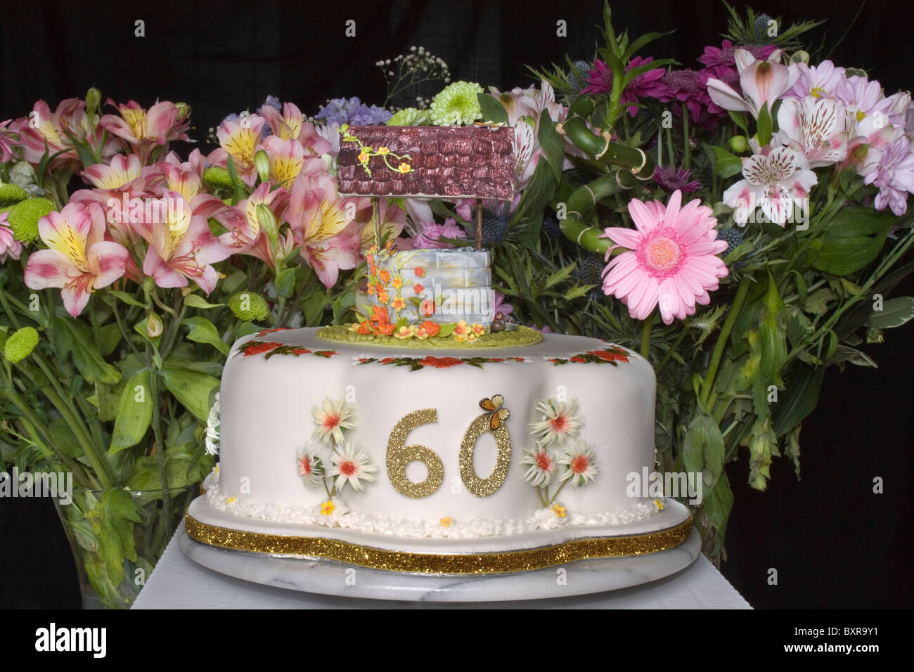 A 60th Birthday Cake With Wishing Well On Top And Cut
