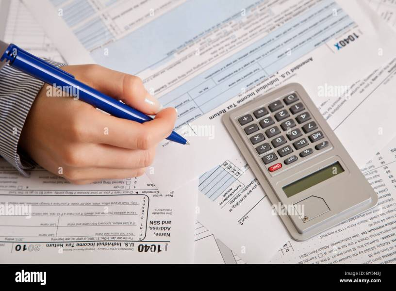 Woman hand filling income tax forms with calculator Stock Photo     Woman hand filling income tax forms with calculator