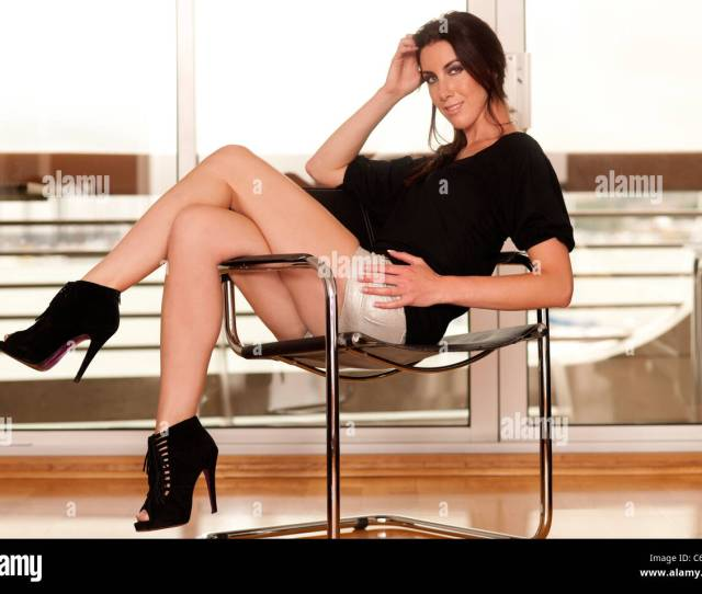Woman Sitting On A Chair With Legs Crossed Sexy With High Heeled Black Ankle Boots