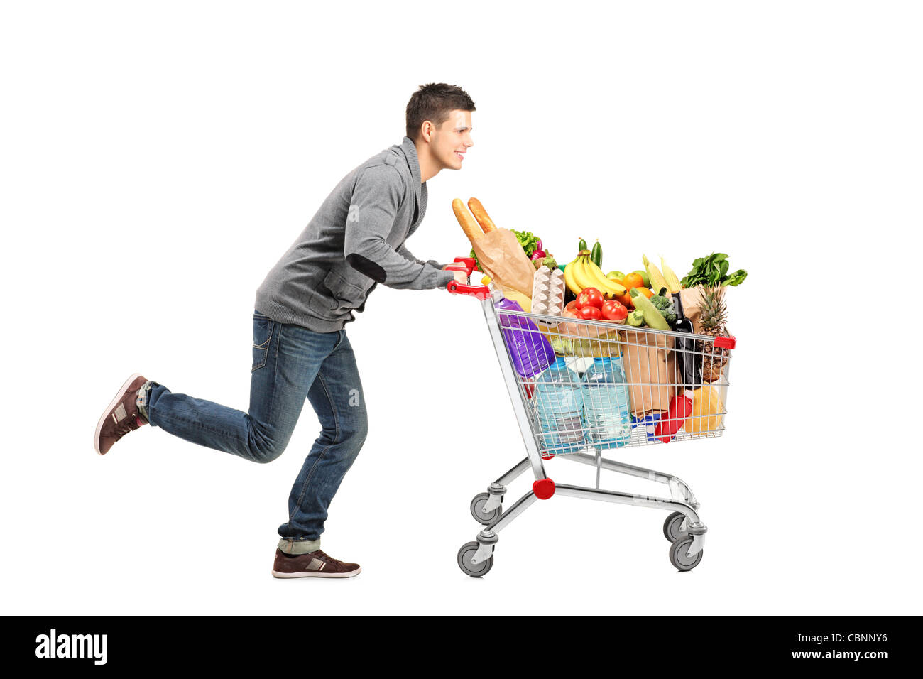 Young Man Running And Pushing A Shopping Cart Full With