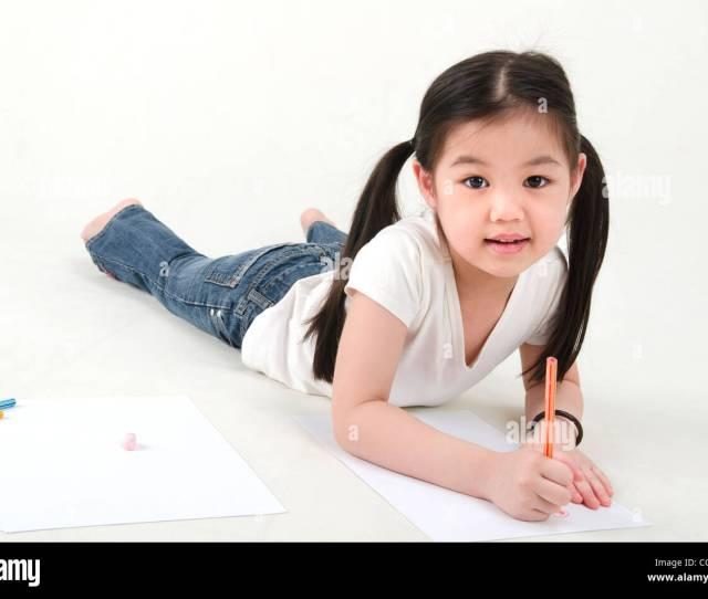 Little Asian Girl Drawing Lying On Floo