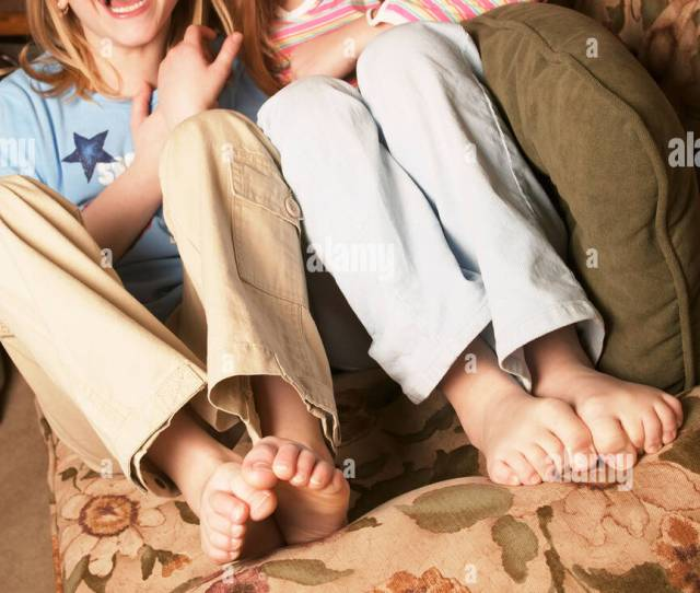 Two Barefoot Young Girls Giggling On Couch