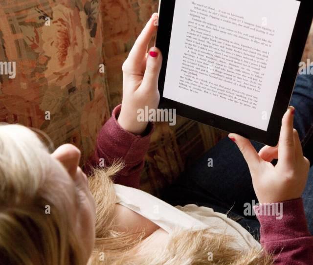 Teen Girl Reading An E Book On An Ipad Uk