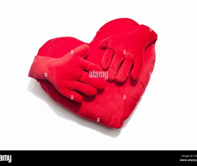 A Red Heart Shaped Cushion With Hands Stock Image