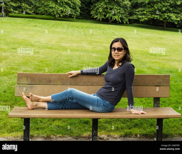 Mature Asian Lady Resting On Cedar Bench With Lush Green Grass And Trees In Background