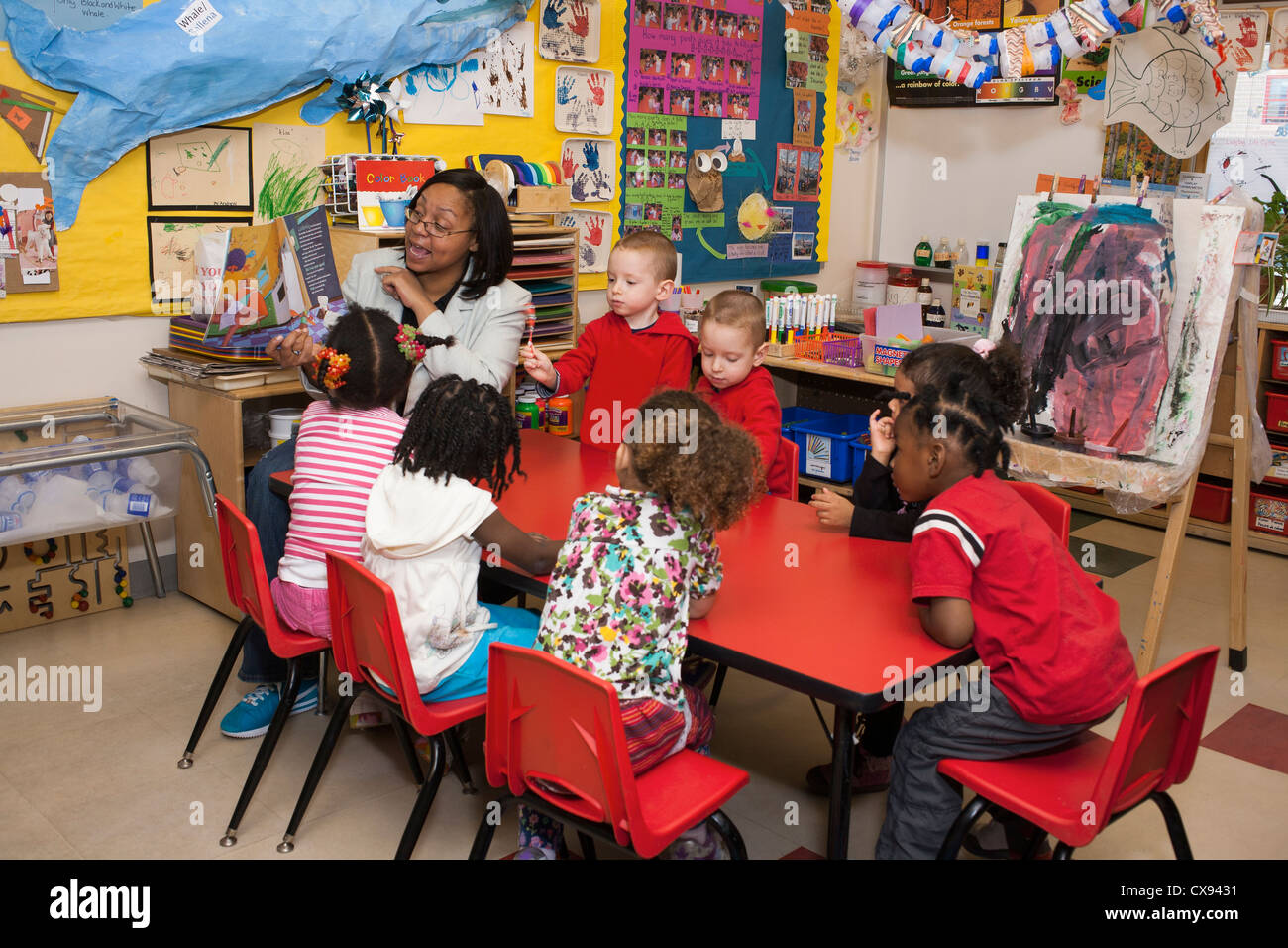 Female African American Preschool Teacher Reading To Her