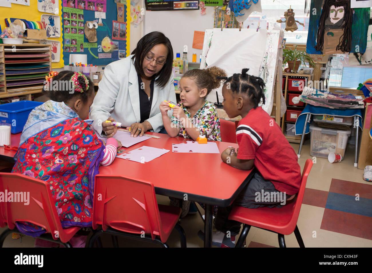 Female African American Preschool Teacher Drawing With
