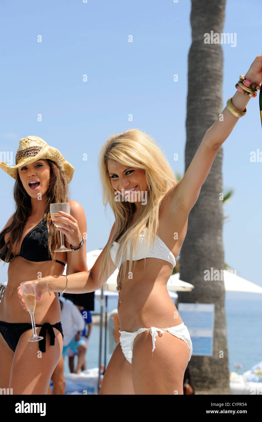 2 Sexy Essex Girlsone Blond And One Brunette In Bikinis With Glasses Of Champagne In Their Hands At Beach Club Party