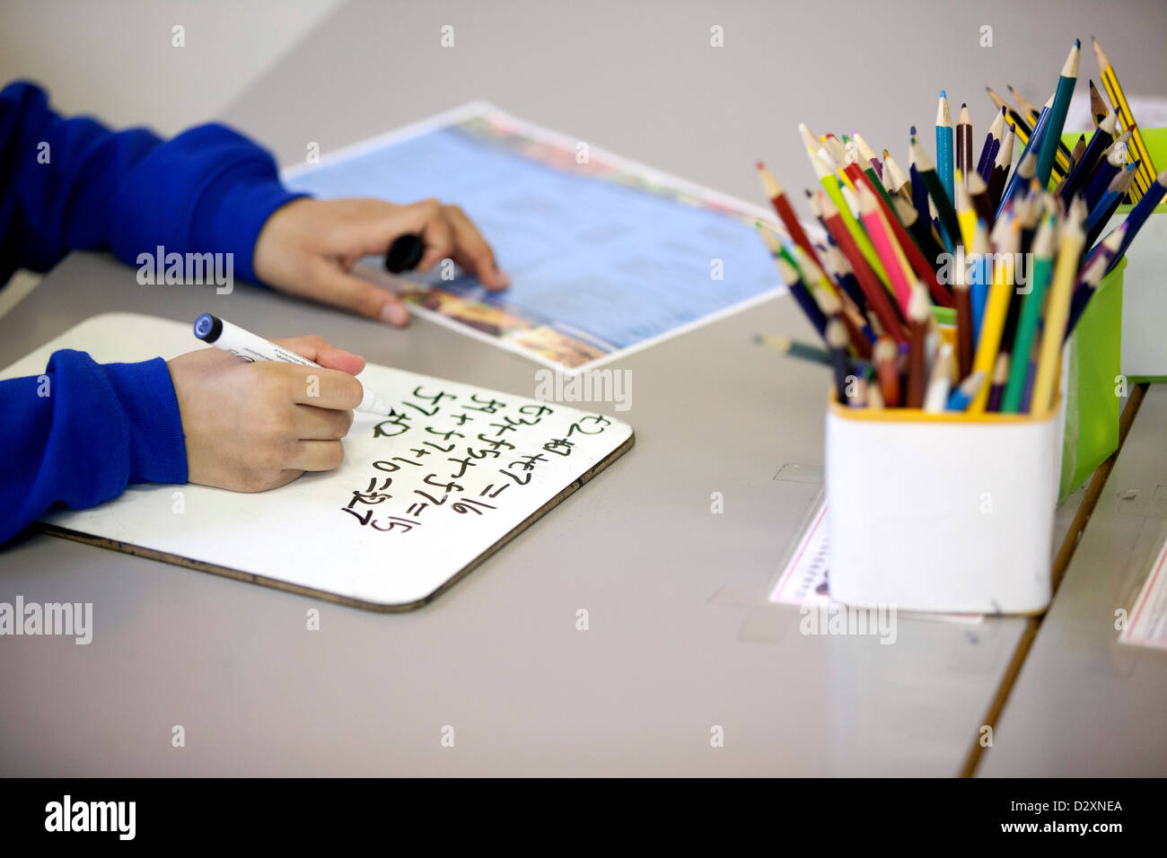 Primary School Child Writing On White Board With Marker Pen Stock Photo