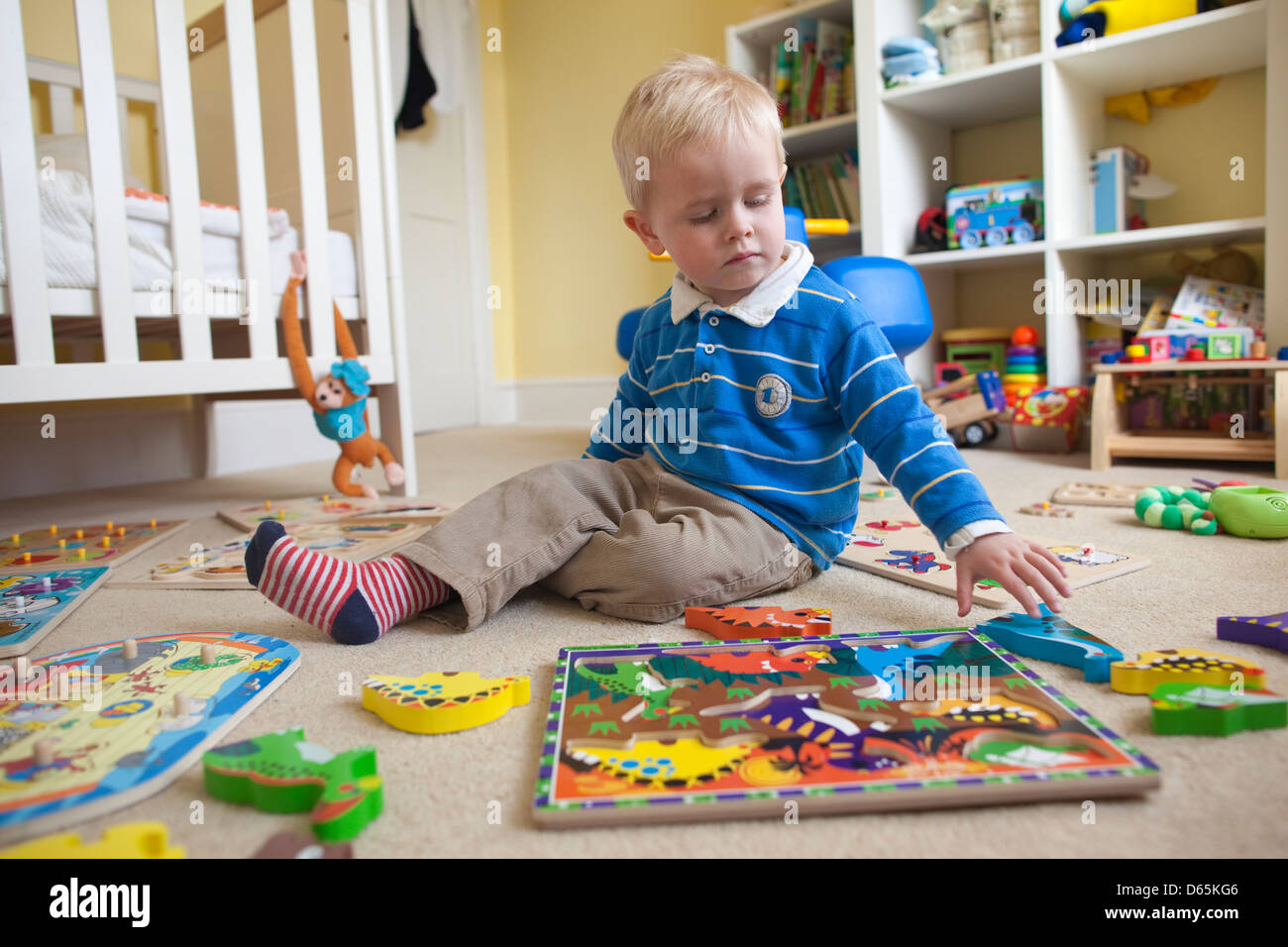 2 Year Old Boy Plays With Various Jigsaw Puzzles In His Bedroom Stock Photo