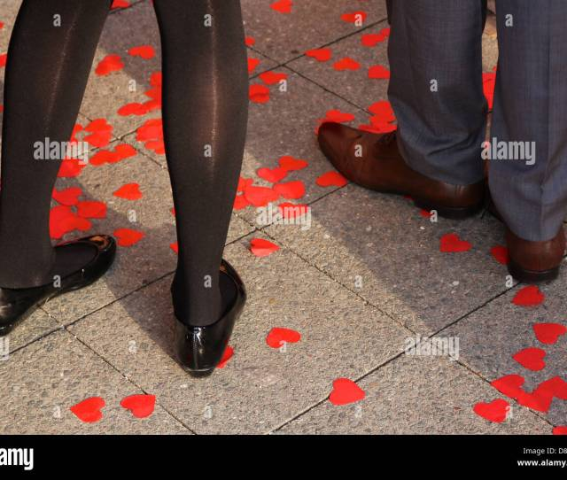 The Lower Legs Of A Couple Standing Among Hearts Sprinkled On The Pavement At A Wedding