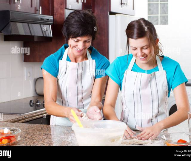 Happy Mid Age Mother And Teen Daughter Baking In Kitchen Stock Image