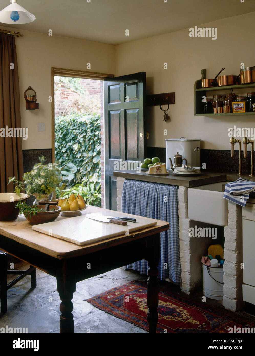 Wooden Table In Center Rustic Country Cottage Kitchen With Curtains Stock Photo Alamy