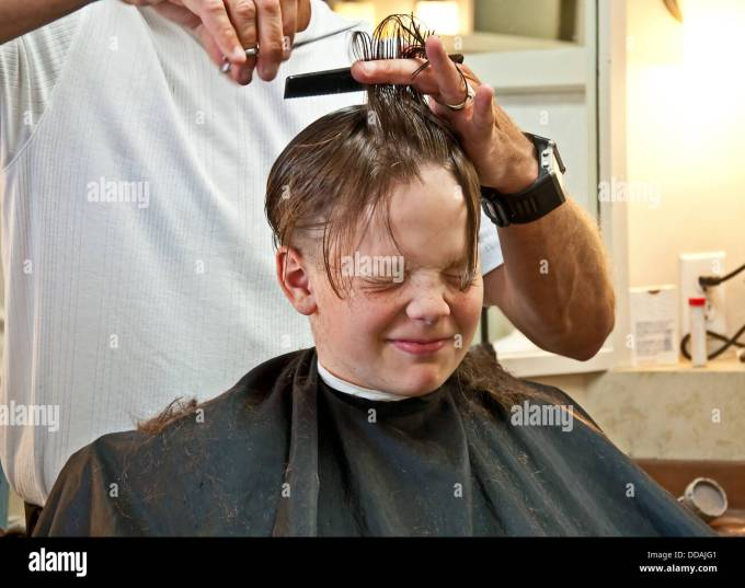this 9 year old caucasian boy is getting his hair cut from