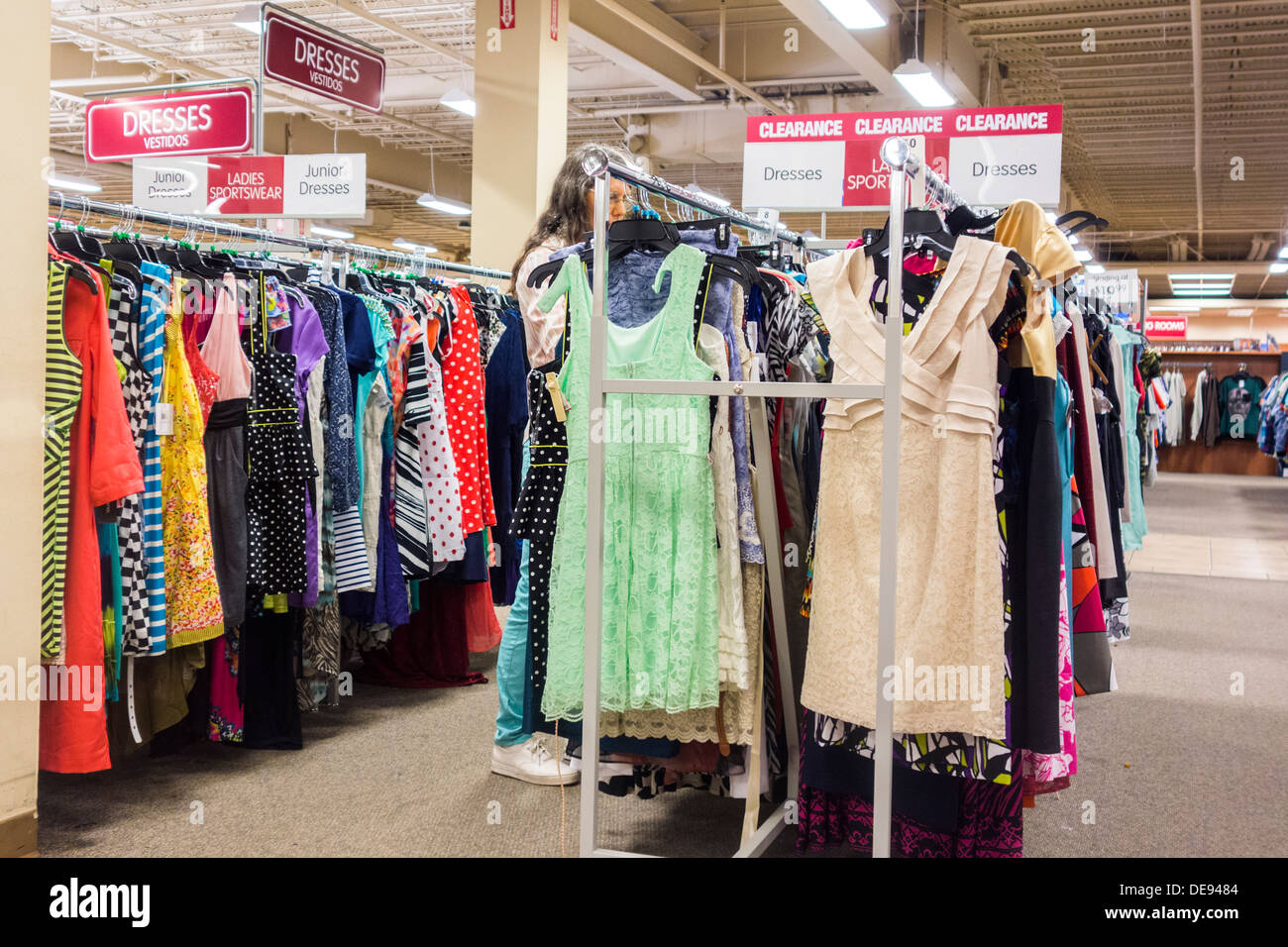 A Woman Browses A Rack Of Dresses On Sale In A Discount