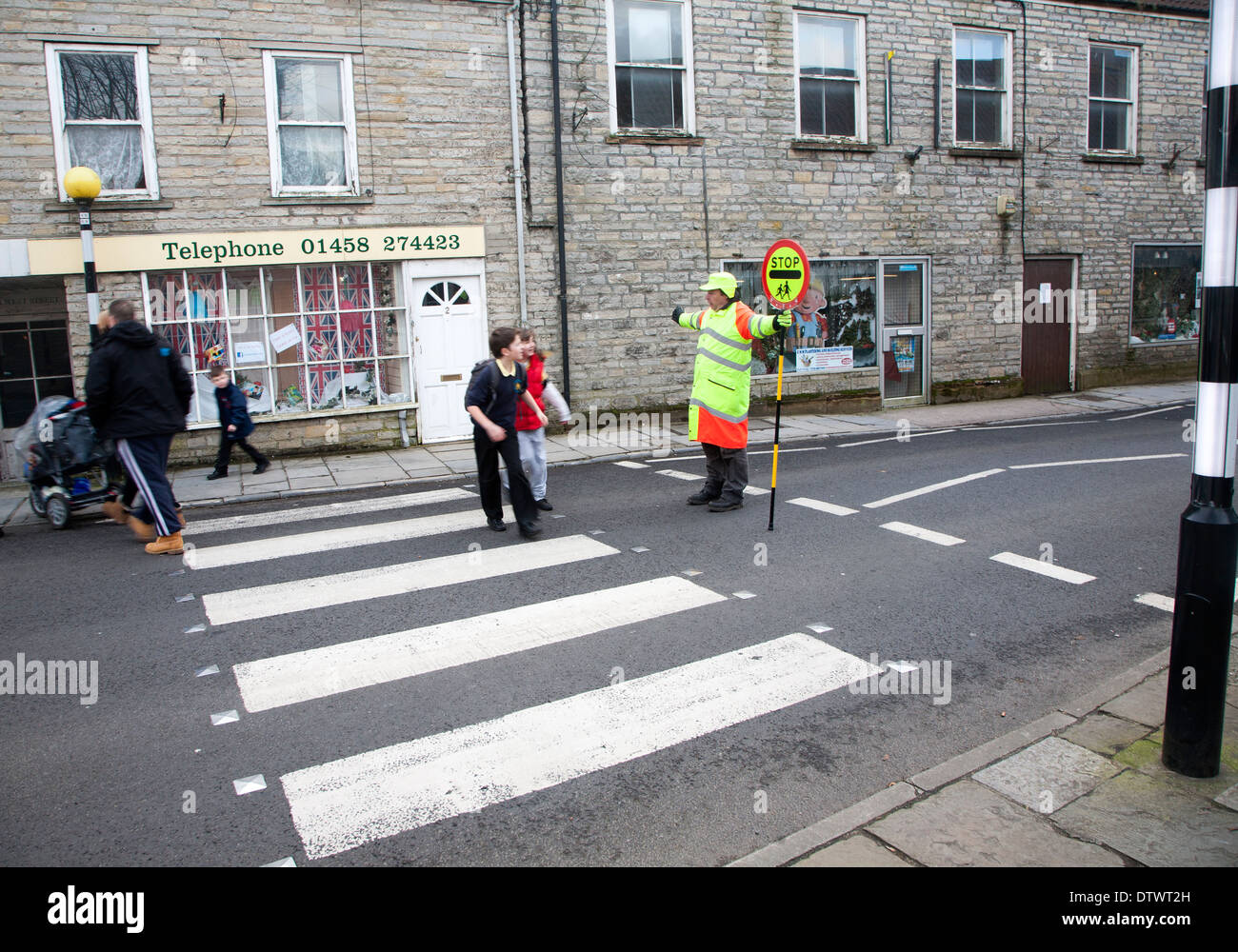 Lollipop Man Stopping Traffic To Allow People To Cross The