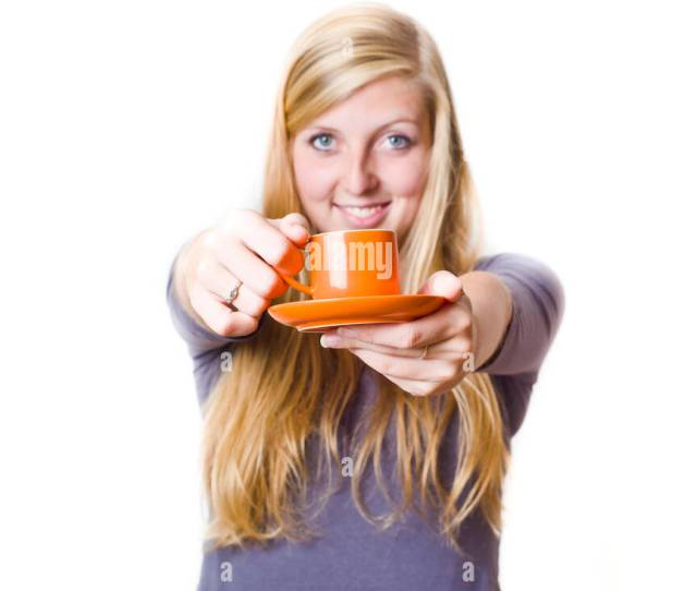 Blond Teenager Girl Smiling And Offering A Cup Of Coffee Stock Image