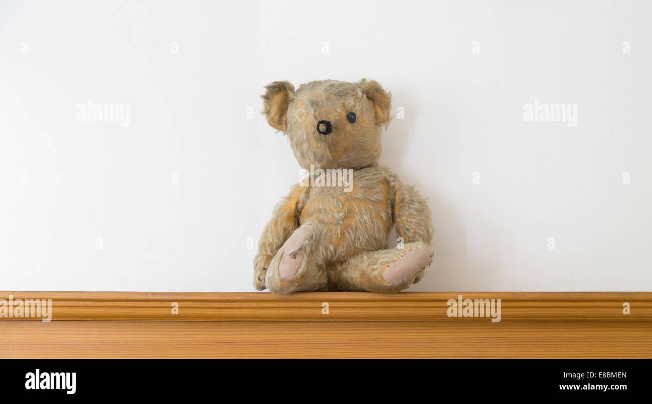 Threadbare One Eyed Teddy Bear On A Wooden Shelf Stock