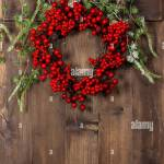Green Christmas Tree Branches And Wreath From Red Berries Over Rustic Stock Photo Alamy