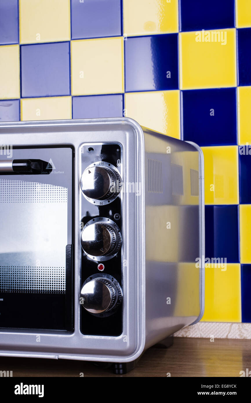 https www alamy com stock photo electric oven gray black color on a background of blue yellow tile 78873107 html