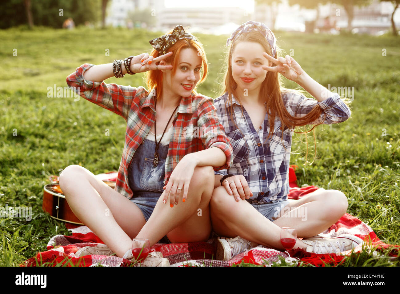 Two Young Smiling Hipster Girls Having Fun At A Picnic In