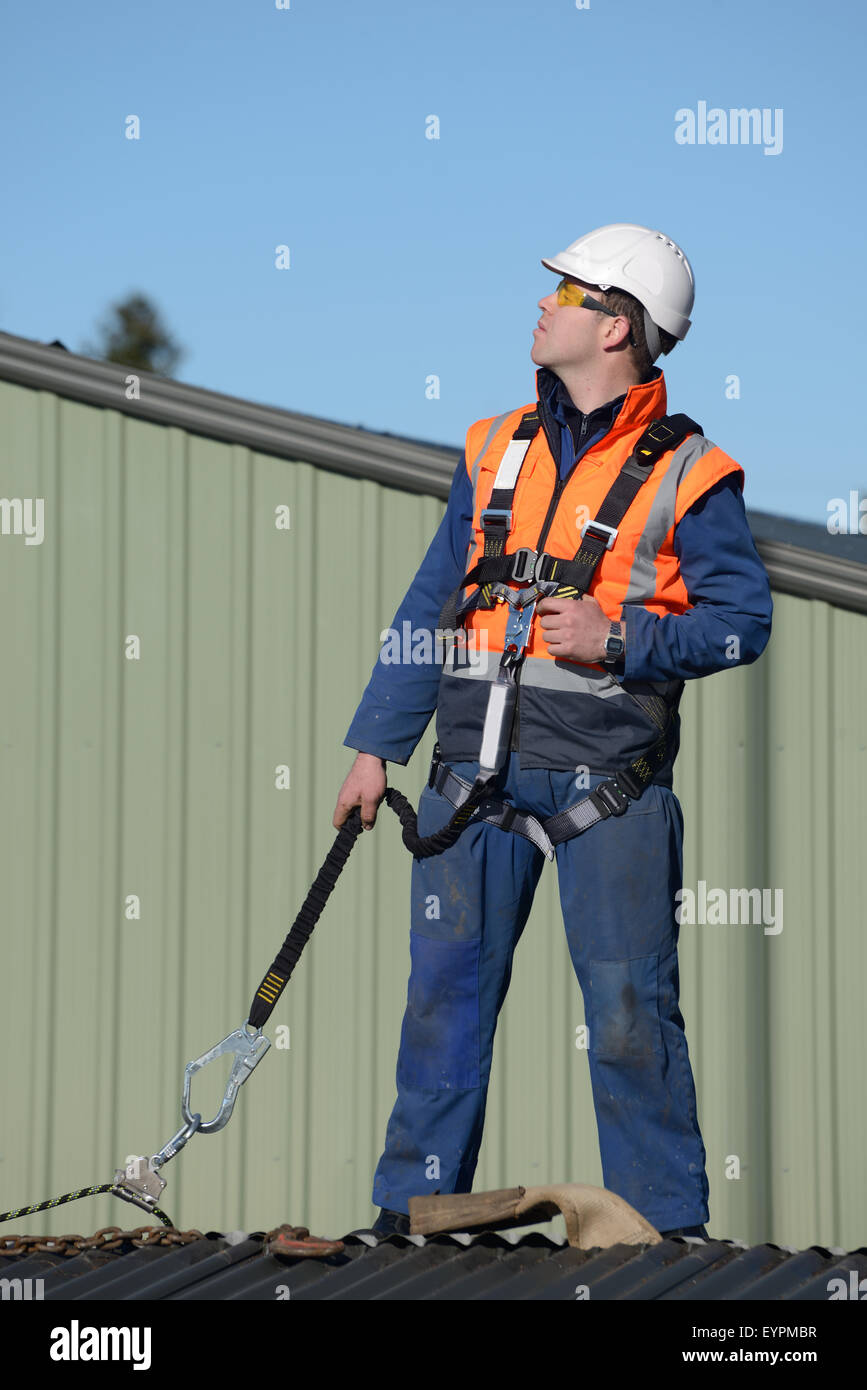 A Builder Wearing A Safety Harness While Working At