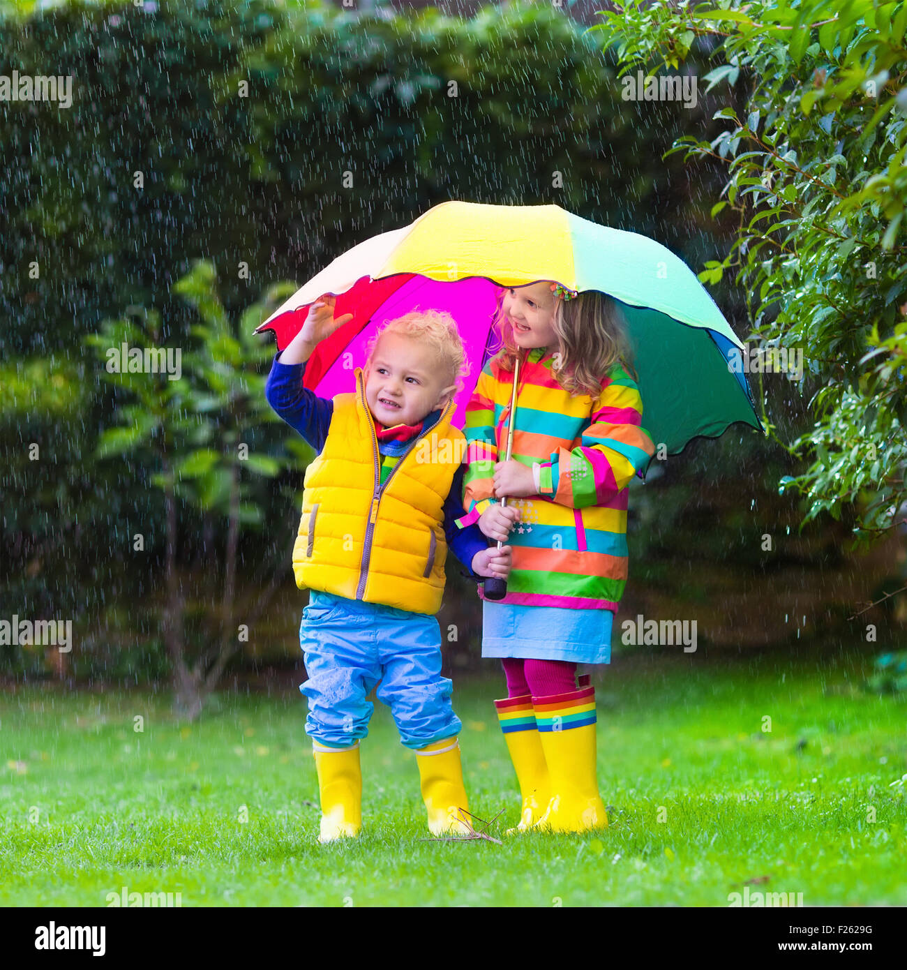 Little Girl And Boy With Colorful Umbrella Playing In The