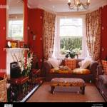 Upholstered Stool And Grey Sofa In Front Of Window With
