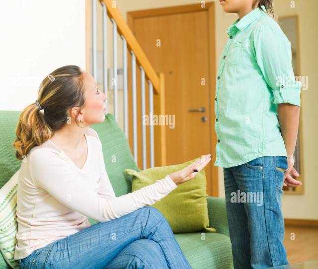 Adult Mother Scolding Naughty Teenage Son In Living Room At Home Stock Image