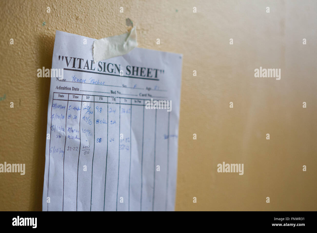 A Patients Vital Sign Sheet Taped To The Wall Above Her Hospital Bed Stock Photo
