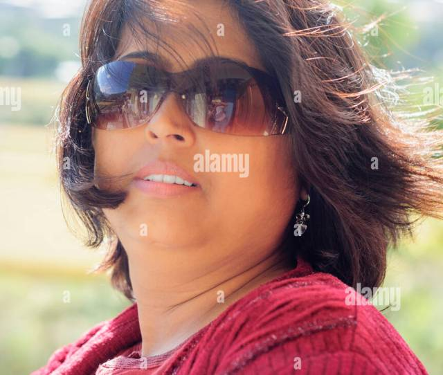 Portrait Of A Mature Asian Non Caucasian Bengali Beautiful Smiling Lady With Copy Space Wearing Red Dress And Backlit