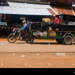 A Man Is Driving A Motorcycle That Is Towing A Trailer With Burnt Stock Photo Alamy