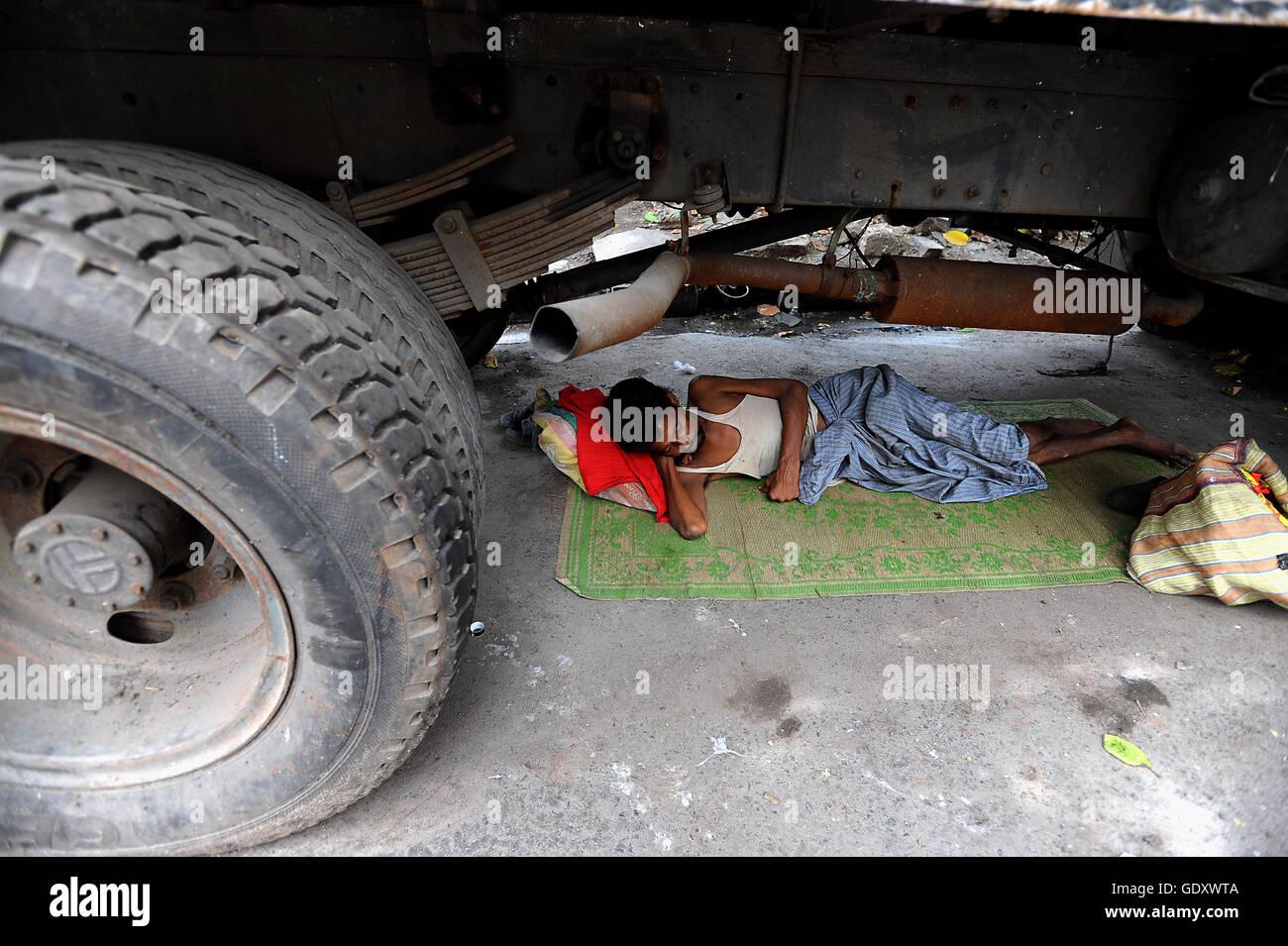 A Man Sleeps Under A Truck In Kolkata Stock Photos