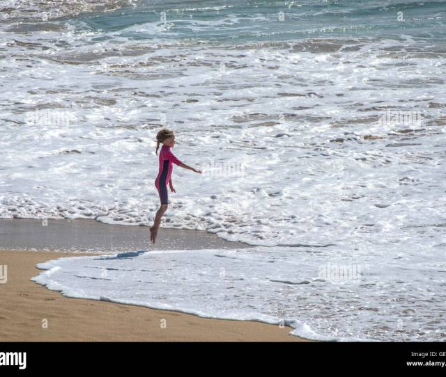 A Young Girl Playing By Herself On Fistral Beach In Newquay Cornwall Stock