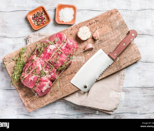 Raw Roastbeef Meat Cut With Hyme And Garlic And Knife On Cutting Board Over Old Wooden Background Top View