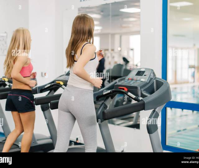 Two Young Girls Running On Treadmills In Modern Sport Gym