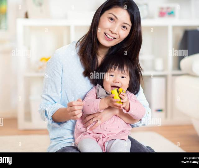 Pretty Happy Japanese Mother Play With Her Cute Little Toddler Daughter At Home Stock Image
