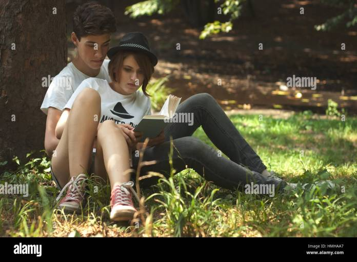 young amazing students couple reading the book in the park. love