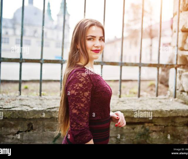 Close Up Portrait Of Young Chubby Teenage Girl Wear On Red Dress Posed Against Iron Fence