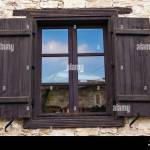 Rustic Brown Wooden Window Shutters With Old Stone Wall