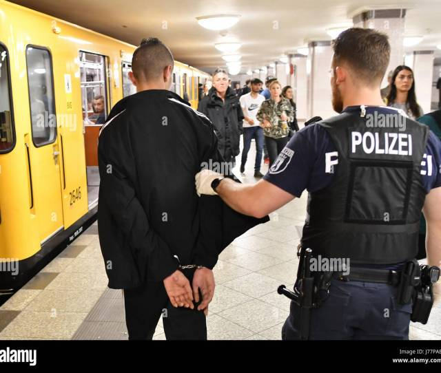 A Police Officer Escorts A Handcuffed Man Suspected Of Pickpocketing In A Train Station In The Borough Of Kreuzberg In Berlin Germany