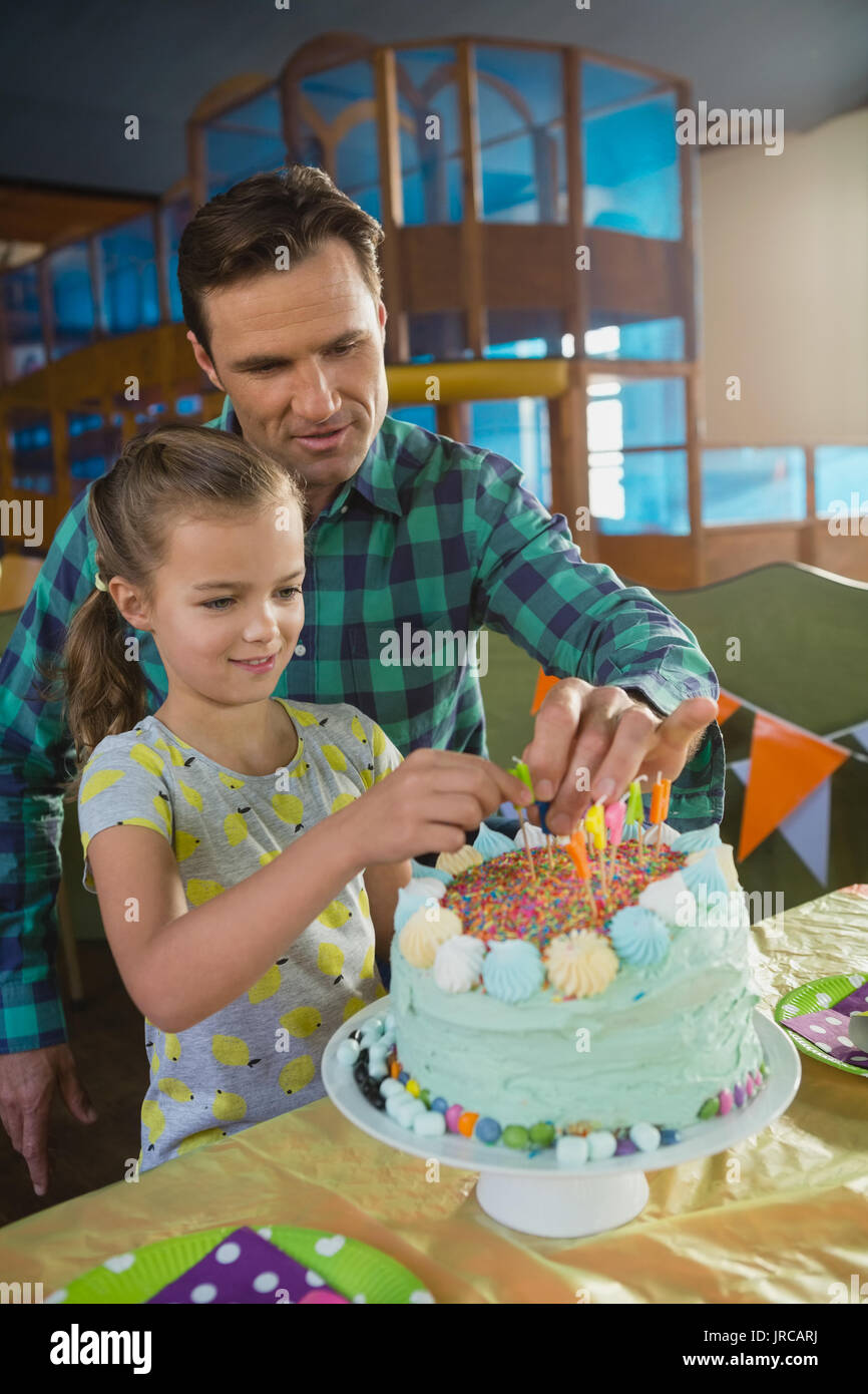 Father And Daughter Decorating Birthday Cake At Home Stock Photo Alamy